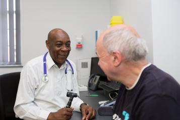 GP speaking to a patient, about to use a thermometer