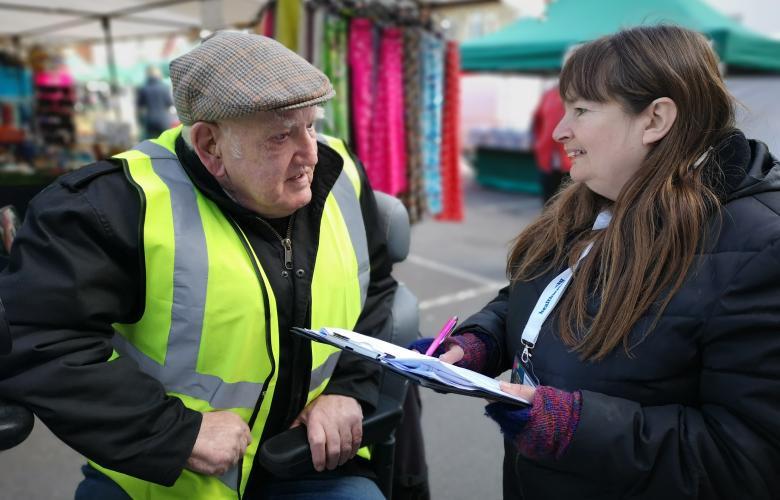 Healthwatch talking to man at market